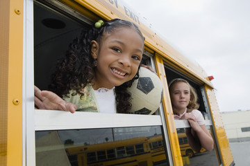 Elementary students looking out from window of school bus
