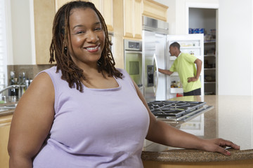 Portrait of an obese African American woman smiling with boy in the background