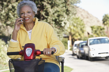 Portrait of an African American senior woman using cell phone as she sits on motor scooter