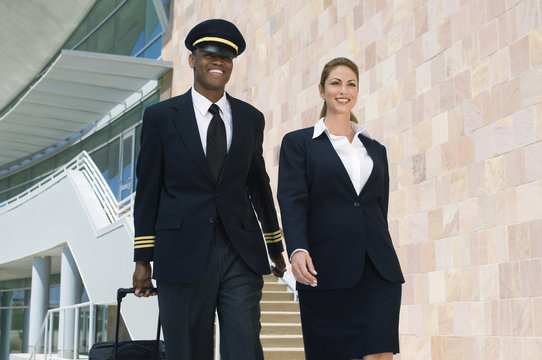 Portrait of happy pilot and flight attendant walking outside building