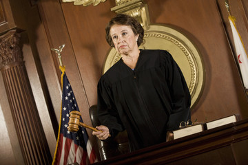 Female judge striking gavel and forming judgment in courtroom