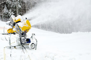 Yellow snow maker machine (snow gun, snow cannon) at ski slopes
