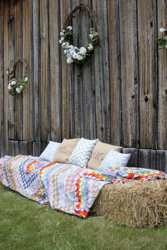 Hay Bales Covered with Quilts on the side of a Barn