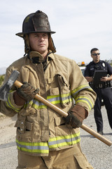 Firefighter holding axe with police officer in the background