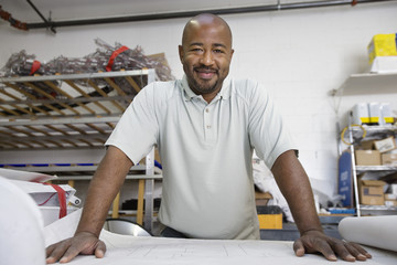 Portrait of happy African American male architect with blueprint at workplace