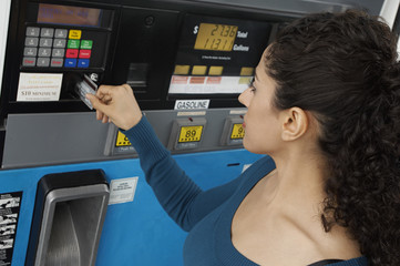 Young woman paying with credit card at gas pump