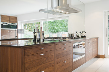 Bottles on countertop with wooden drawers in modern kitchen