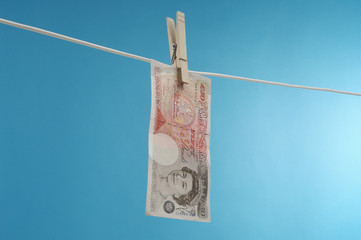 British paper currency on clothesline against blue background