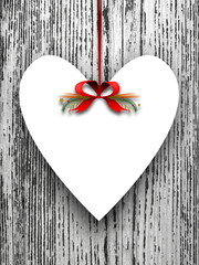 Blank heart shaped ornament frame hanged by red Christmas ribbon against rough gray wooden boards background