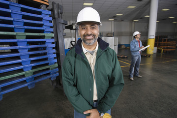 Portrait of a smiling man with colleague in the background at factory