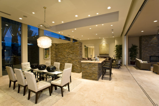 Dining area against kitchen with living room in background at modern house