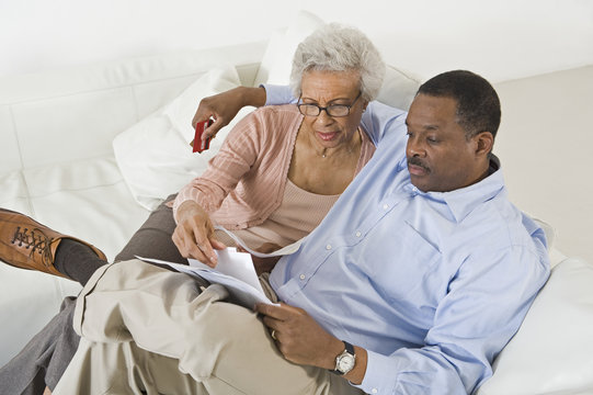Tensed African American couple looking at bills worried with home finances