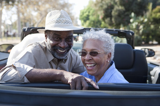 Portrait of happy mature couple at the back seat of car smiling