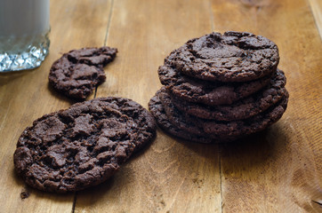 Photo of freshly baked chocolate chips cookies on wooden board