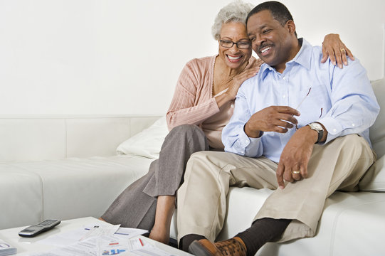 Happy African American senior couple sitting on sofa at home