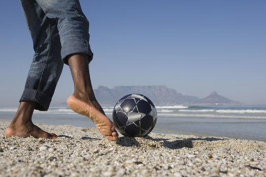 Lowsection of a man playing soccer on beach