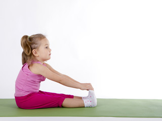 Kid girl doing fitness exercises.