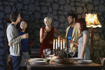 Group of multiethnic friends enjoying drinks by dining table