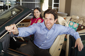 Portrait of a happy man holding out car key with woman sitting beside him in a convertible