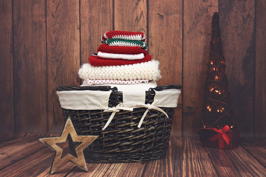 Red, white and green knit Christmas clothes in a wicker basket with Christmas tree