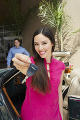 Portrait of a beautiful female holding car key with man standing in background