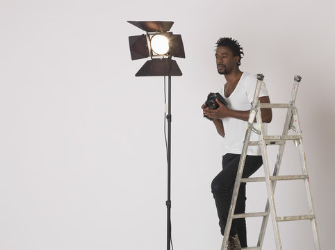 Portrait of an African American male photographer holding camera in studio