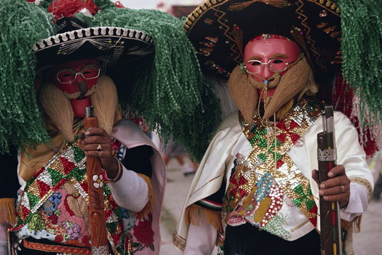 Portrait of two men wearing masks, costumes, sombreros and carrying guns, during the Huejotzingo Carnival in Mexico