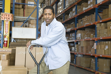 Portrait of a content worker leaning on trolley in distribution warehouse