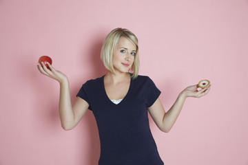 Portrait of a happy young female choosing between apple and tart against pink background