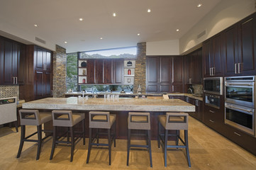 View of a spacious kitchen with stools at the island in modern house