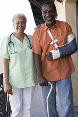 Portrait of an African American disabled patient standing with doctor in hospital