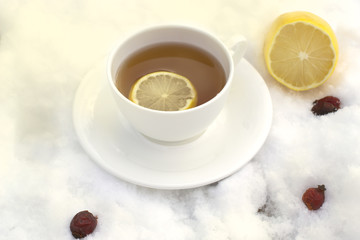 white mug of tea on a saucer with a lemon and wild rose on snow