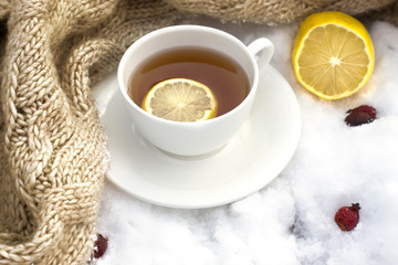 white mug of tea wrapped in a knitted scarf on a saucer, lemon a