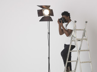 Male photographer taking photos with camera in studio