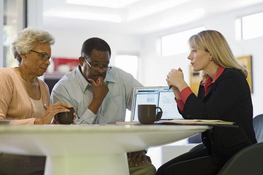 Serious African American couple in a meeting with female financial advisor at home