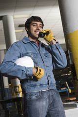 Smiling young man using telephone in the factory