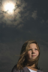 Closeup of a thoughtful little girl against the sky
