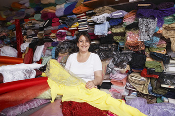Portrait of confident female fabric store owner standing at counter