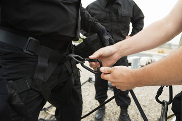 Closeup midsection of SWAT Team preparing with climbing equipment