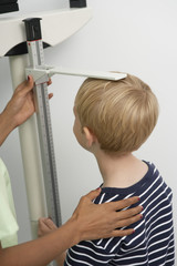 Female nurse measuring boy's height in the clinic