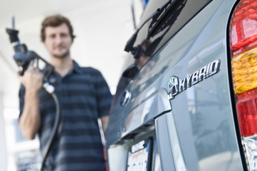 View of a blurred man refueling a cropped hybrid car