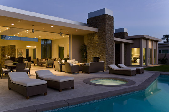 Spacious house exterior with sunloungers on patio by swimming pool at dusk