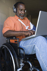 Injured African American man using laptop and listening music while sitting on wheelchair