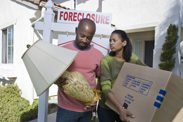 Multiethnic bankrupt couple carrying lamp and cardboard box while moving out of house