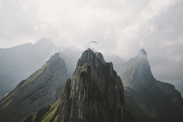 Paraglider flying over tall mountain structure and through clouds on a bright and hazy day