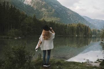 Blonde young adult woman wearing a poncho and a hat enjoying a morning in the forest at a mountain lake
