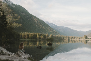 Blonde young adult woman wearing a blue jeans jacket enjoying a morning in the forest at a mountain lake