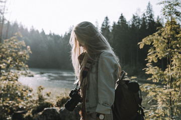 Portrait of a Blonde young adult woman photographer wearing a jeans jacket and a backpack standing in a forest in front of a lake at sunrise