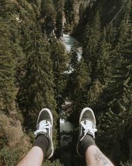 Legs of Adult male with a tattoo wearing black shoes sitting and overlooking a river and pine trees at bright daylight