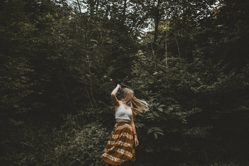 Beautiful blonde young adult woman dancing in the forest with flying hair